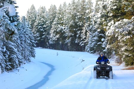 Man riding snowmobile or fourwheeler on the country side trail near water canal.