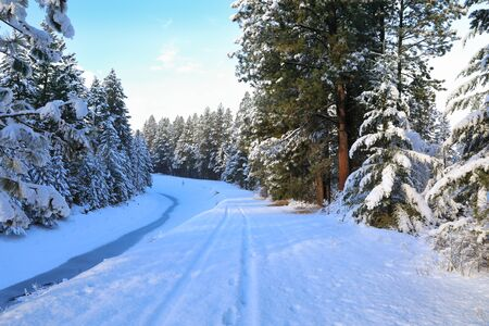 SNow covered beautiful old American rustic country side landscape with bridge, trail and water canal. Peaceful and inspiring. Banque d'images