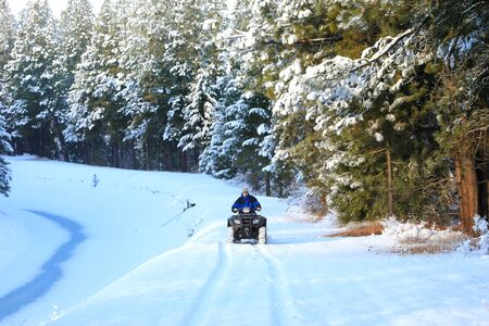 Man riding snowmobile or fourwheeler on the country side trail near water canal. Banque d'images - 142950462