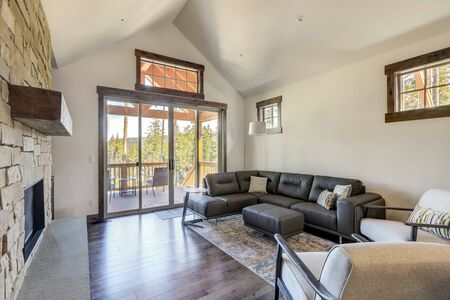 Beautiful large bright vaulted ceiling white walls living room interior with stone and leather sofa and dark grey hardwood.