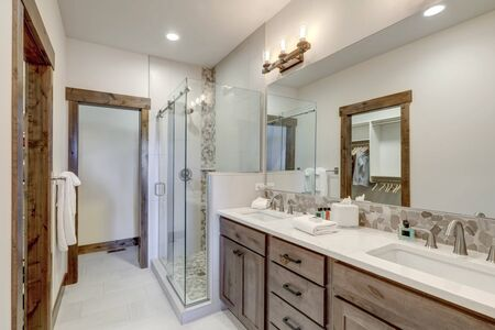Grey and brown natural bathroom interior with white countertops.