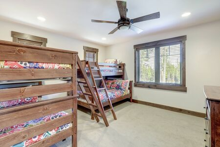 Bright new bedroom with two bunk beds with colorful bedding and ceiling fan. Zdjęcie Seryjne