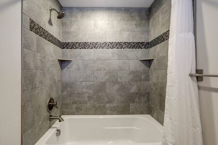 WHite new tub details with curtain and grey tiles.