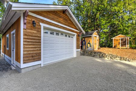 Detached free standing large garage or shop natural brown tone with white trim and green summer nature.