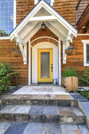 Wooden large American house with natural brown tone with white trim and green summer nature with yellow front door.