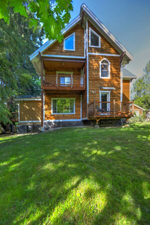 Wooden large American house with natural brown tone with white trim and green summer nature.