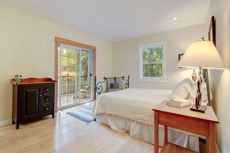 Bedroom bright interior with metal bed and sliding door to the balcony with chair, country style of American cozy home with light bamboo flooring.
