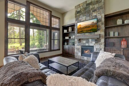 Luxury cozy living room interior with grey stone and rich wood with fuzzy blankets and large windows and TV.