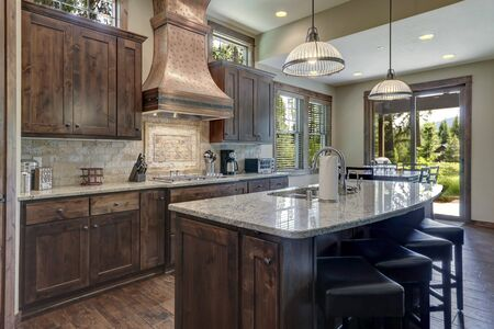 Luxury dark wood rich kitchen interior with copper stove hood and grey natural stone backsplash.