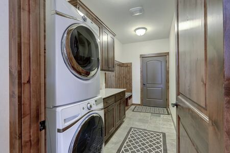 Laundry interior with beautiful wood doors and trim. Washer and dryer stuck on top of each other.
