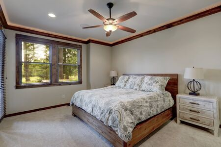 Bedroom interior with beige walls and wood trim and ceiling fan.