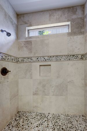 Classic simple small bathroom interior detailes walk in shower with natural stone on the floor.