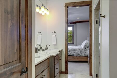Classic simple small bathroom interior detailes with rich dark wood closet door and open door to the bedroom.