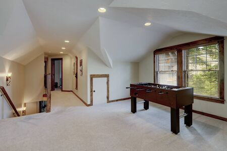 Hockey play table in upstairs family play room with vaulted ceiling.