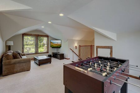 Hockey play table in upstairs family play room with vaulted ceiling with TV and sofa.