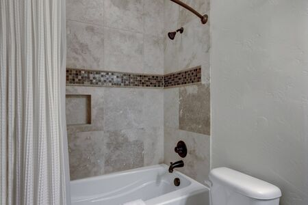 Classic simple small bathroom interior detailes with natural stone around bath tub.
