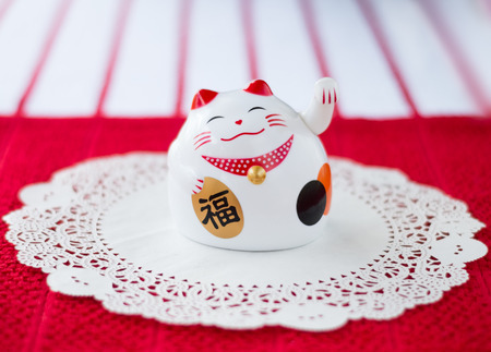 maneki: Maneki neko on a doilie on a red and white background. This beckoning cat is believed to bring luck, prosperity and fortune.