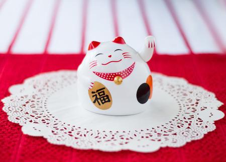 se�al de silencio: Neko de Maneki en un Doilie sobre un fondo rojo y blanco. Se cree que este gato que tienta para traer suerte, la prosperidad y la fortuna. Foto de archivo