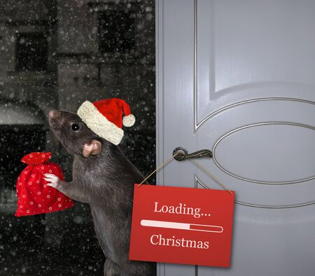 The black rat in a Santa Claus hat with a red bag of gifts is standing near the open door on which there is a sign with the inscription loading Christmas.