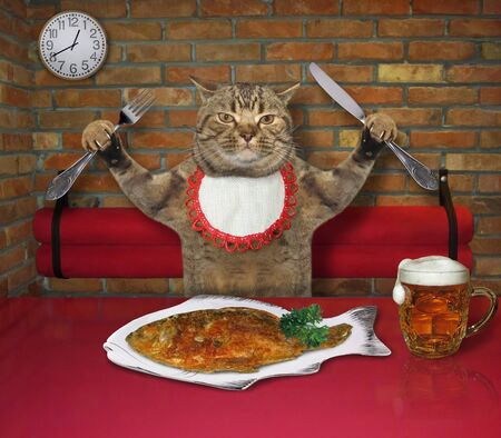 The beige cat in a neck napkin with a knife and a fork is eating grilled fish with beer at a table in a restaurant.