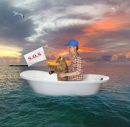 The man in a red cap with his cat are drifting in a bathtub on the open sea after a shipwreck. The cat holds a sign that says sos.