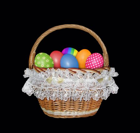 The wicker basket decorated with white lace and filled with colorful easter eggs. Black background. Isolated.