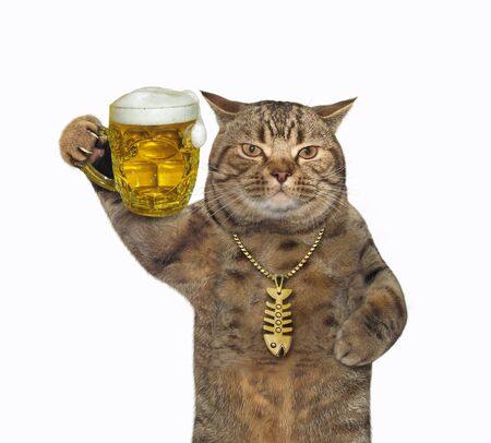 The beige cat in a gold fish-bone pendant is drinking light beer from a mug. White background. Isolated. 版權商用圖片
