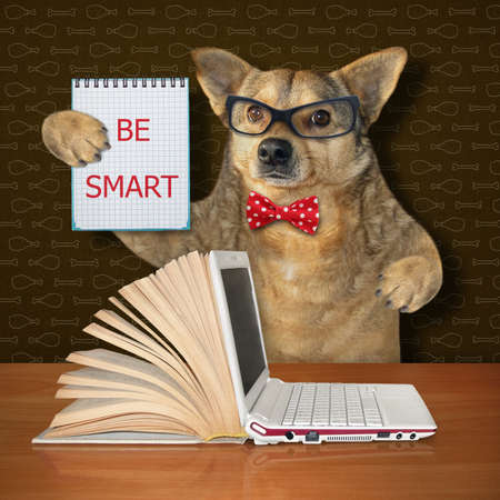 The beige dog in glasses and a red bow tie is sitting at the wooden table with a open book and a laptop. He holds a notebook with the inscription be smart.