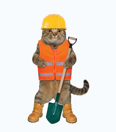 The beige cat worker in a vest, a helmet and boots is holding a shovel. White background. Isolated.