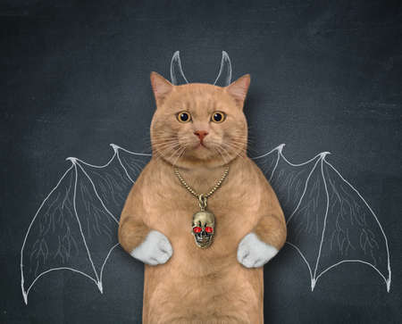 A reddish cat stands by a blackboard with bat wings and horns painted on it.