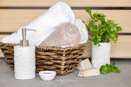 colored bottle: soap,herbs and towels in a wicker basket on a light background Stock Photo