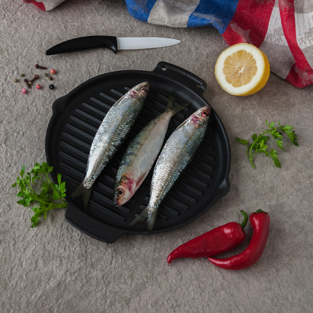 lieing: Fresh sardines on the cast-iron frying pan, ready to be cooked with pepper. Omega 3. Fish with herbs. Mediterranean fish on frying pan with pepper and a knife lieing near