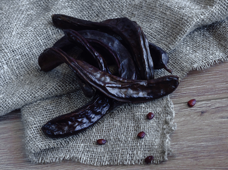group of dried carob pods with seeds on background 版權商用圖片
