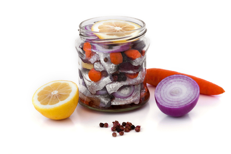 Marinated herring with spices in a glass jar