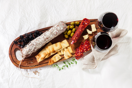 Italian snacks on a wooden board with wine. Whole salami and different types of olives. Traditional Mediterranean table