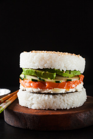 sushi menu with burger made from rice and smoked salmon, avocado, light cheese and nori Фото со стока - 85408815
