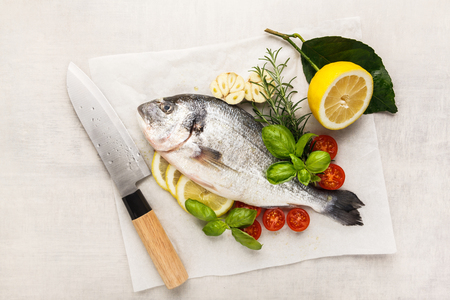 Fresh uncooked dorado or sea bream fish with lemon, herbs, oil, vegetables and spices in a frying pan on a baking paper over white backdrop, top view Stock Photo