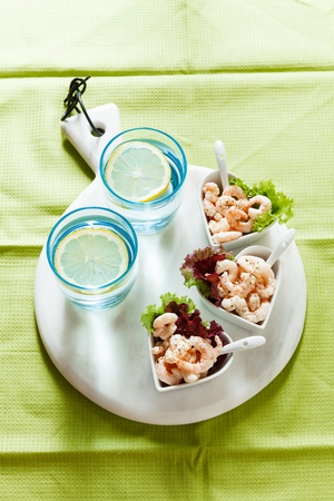 Prawn cocktail  in serving bowls in the form of hearts on a gray background. On a marble cutting board. Two glasses of water with ice