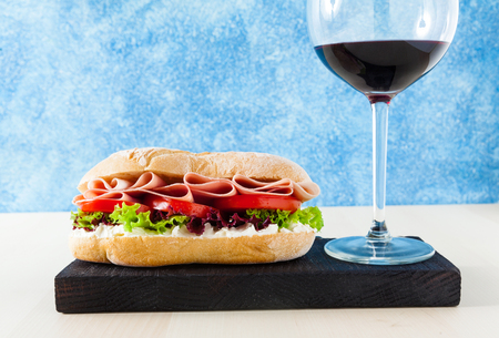 A Panini sandwich with ham, tomatoes and fresh lettuce leaves and a glass of red wine. blu background, copy space Фото со стока