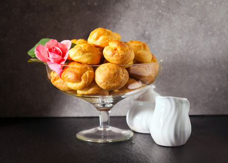 profiteroles and coffee Served in a vase for sweets and a rose Stock Photo
