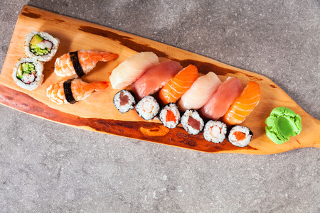 Various kinds of sushi served on a platter with soy sauce, wasabi and pickled ginger. Stock Photo
