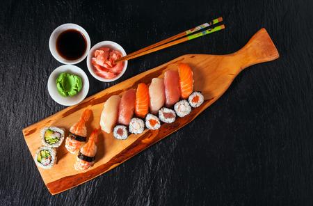Sushi Set gunkan, nigiri and rolls served on black stone background