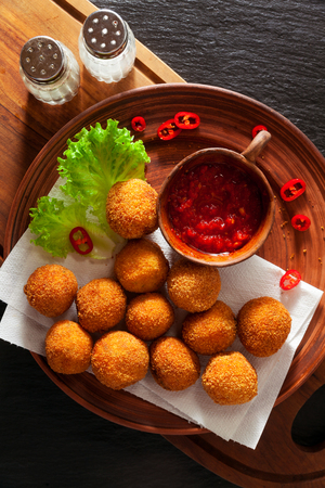Traditional italian fried balls of mozzarella with spicy souce. figher food  Archivio Fotografico