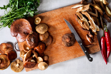 whole and cut mushrooms on a cutting board. process of cutting and cooking on a gray stone table  Stockfoto