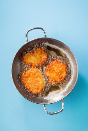 potato pancakes latkes are cooked in oil on a metal frying pan on a blue background