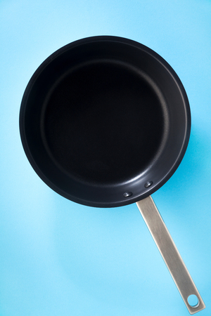 empty pan with non-stick coating and a steel pen isolated on blue
