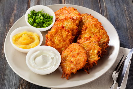 Potato pancakes, latkes or boxty and sauces from sour cream, yogurt, apple sauce and finely chopped green onion on a wooden table of boards 스톡 콘텐츠