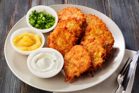 Kartoffelpuffer, Latkes oder Boxty und Saucen aus Sauerrahm, Joghurt, Apfelsauce und fein gehackten Frühlingszwiebeln auf einem Holztisch aus Brettern
