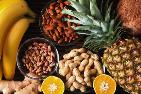 Healthy food clean eating selection in wooden box: fruit, superfood, nuts on black  concrete background. bananas, pineapple, pears, ginger, coconut, almonds, peanuts and pistachios