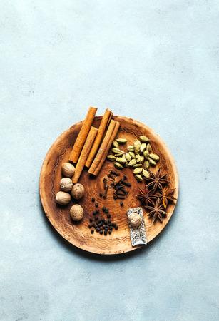 Spice collection on the plate : cinnamon sticks, nutmeg, anise, cardamom, black pepper, cloves. on blue table background.